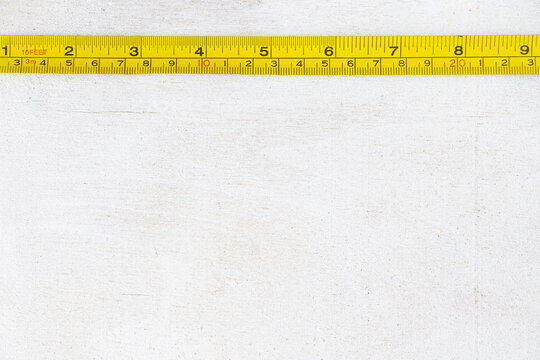 Top view of a yellow steel tape measuring a white wooden surface with space for text