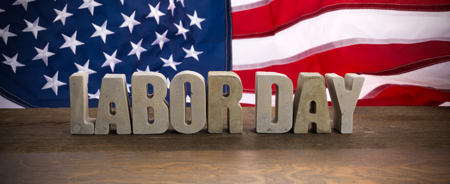 Happy Labor Day banner. USA flag and letters on rustic wooden background.