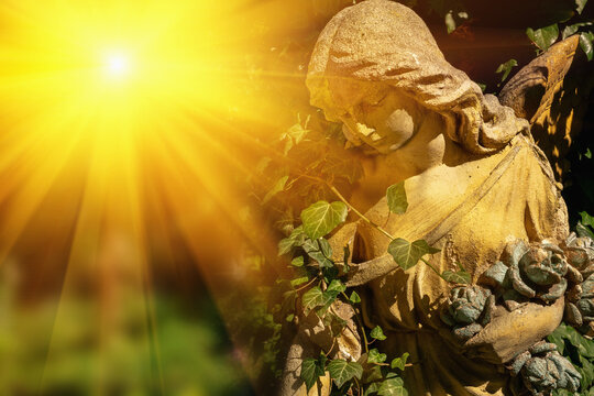 Antique statue of angel with sad expression that looks up in the sunlight.