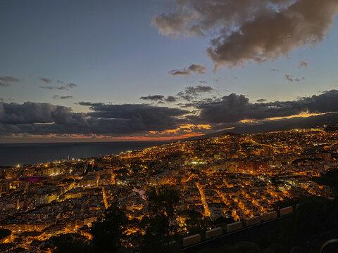 Ciudad de Santa Cruz de Tenerife en el atardecer con algunas nubes de fondo el mar se observa la ciudad urbana con el alumbrado de las luces de las calles