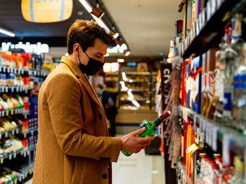 handsome man wearing a protective mask during the covid-19 in the supermarket taking groceries on the shelf