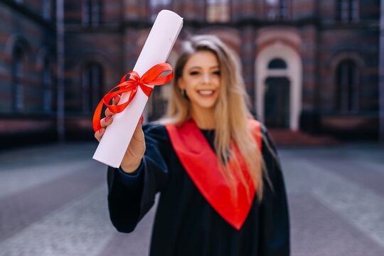 Graduates on the last day of their studies. female student smiling happily wearing graduation clothes, proud, showing diploma.