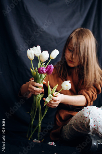 The girl with tulips on a dark background. Happy Mother's Day