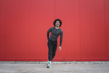 Fototapeta Cheerful caucasian curly-haired man dancing against a red wall outdoors in Spain