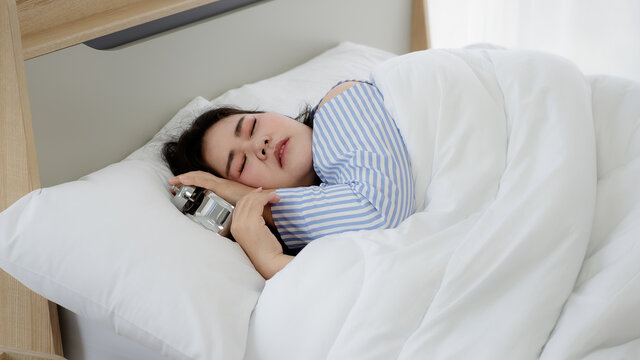 Asian young chubby oversized obese woman wears blue stripe pyjama snore and have deep sleep sweet dream in bed cover by white blanket turn off and hug metal alarm clock in hotel bedroom morning