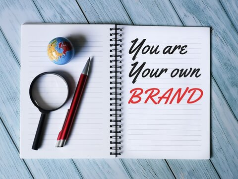 Business and finance concept. Selective focus notebook written you are your own brand with pen,mini globe and magnifying glass.