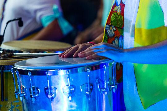 Closeup shot of a man playing drums at the carnival at night