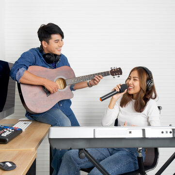 Young asian woman sings while playing an electric keyboard in front of white walls. Her boyfriend played the guitar together. Musicians producing music in professional recording studio.