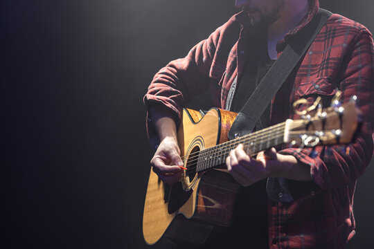 Acoustic guitar in the hands of a guitarist.