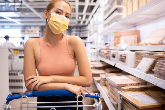 young asian woman with medical mask looking and shopping in the warehouse store during coronavirus (covid-19) pandemic. .After quarantine due to coronavirus outbreak with new normal lifestyle.
