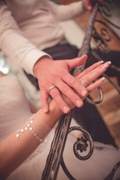 Closeup shot of newlyweds hands on each other showing their rings during their wedding ceremony