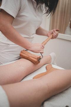 Vertical closeup shot of a masseuse using a wooden roller on a clients legs