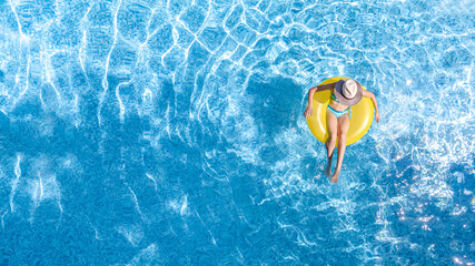 Fototapeta Active young girl in swimming pool aerial top view from above, child relaxes and swims on inflatable ring donut and has fun in water on family vacation, tropical holiday resort