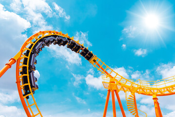 roller coaster high in the summer sky at theme park most excited fun and joyful playing machine