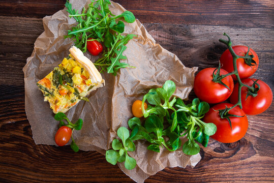 Fresh vegetable casserole with salad served on a rustic wooden board