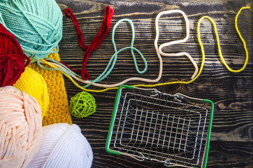 skeins of colored yarn, an empty basket and the word