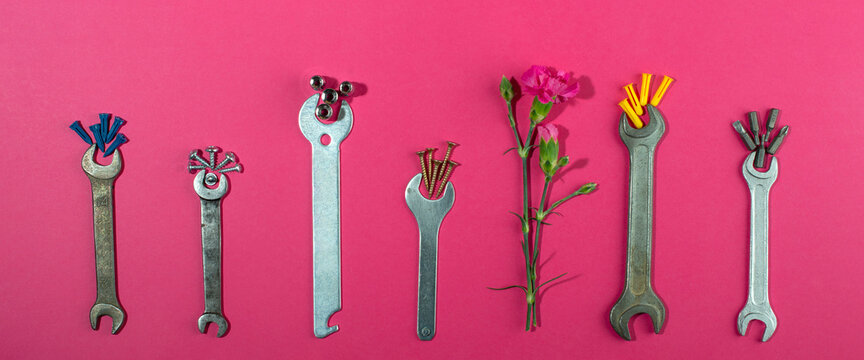 Labor Day background concept, 1 May concept. Wrench and clove pink carnation flower on pink background.