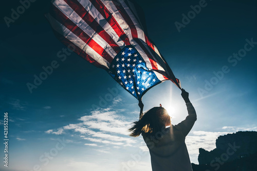 Woman with American flag on the beach. 4th of July. Independence Day. Patriotic holiday.