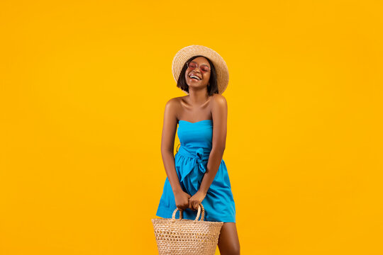 Beautiful black woman in summer outfit holding beach bag, laughing and enjoying her vacation on orange background