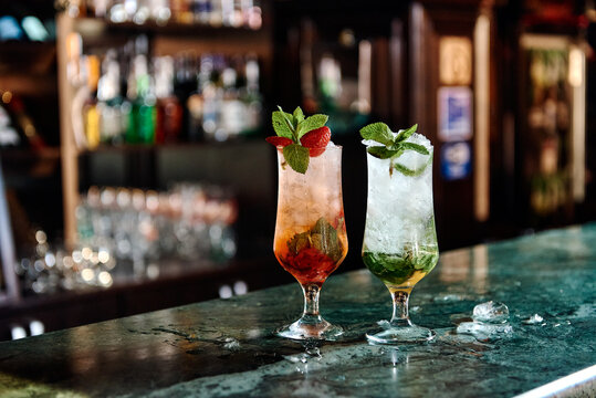 two mojitos with mint tonic and iced strawberry decor stand on a green bar with a blurred background