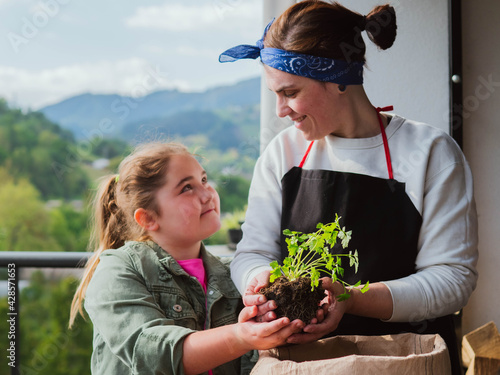 Happy Mother's Day! child daughter plants flowers together with her mother on vacation.