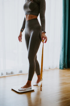 Woman step on Weighing Scale for Measuring Body Weight At Home. . Close up of a woman legs measuring weight with scale at home and holding measuring tape. Weight loss control