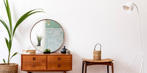 Minimalistic and stylish composition of living room with wooden commode, mirror, chair , lamp,...