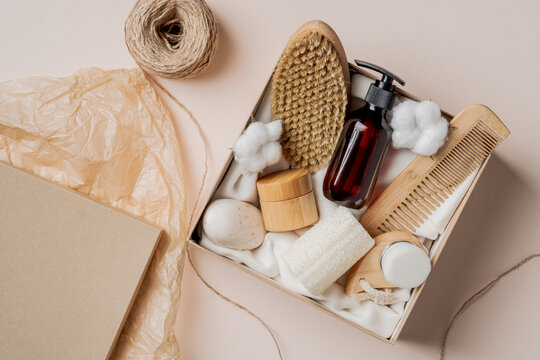 Beauty box with natural personal care cosmetics. Body brush, hair comp, amber glass shampoo bottle, moisturizer, cotton. Flat lay, top view.