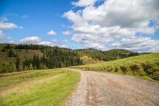 road on a background of forest and hills and fields blue sky with clouds. Landscape nature.