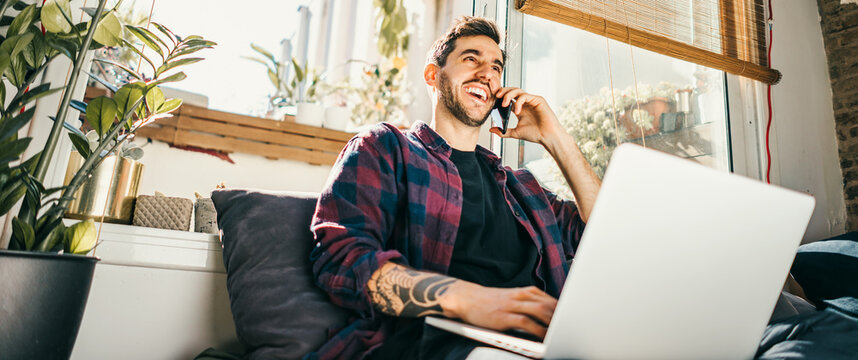 Young man with laptop and smartphone at home. Freelancer. Concept of remote work or study.
