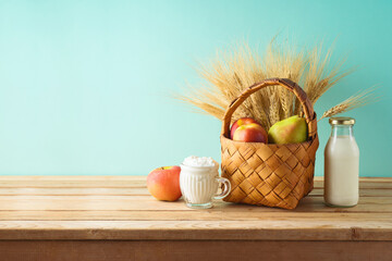 Jewish holiday shavuot background with fruit basket and milk bottle on wooden table
