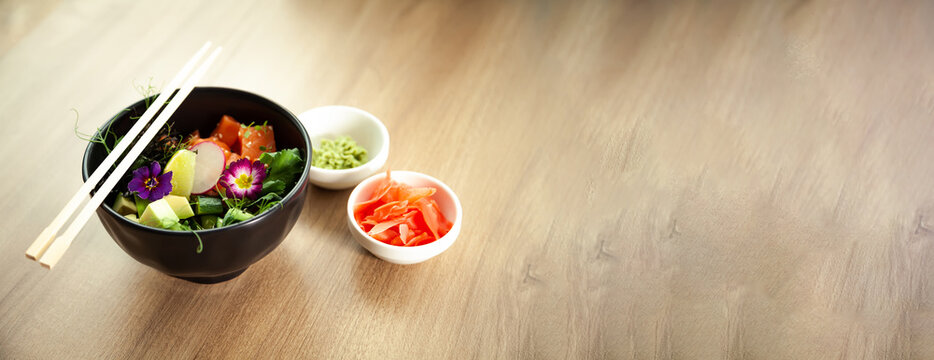 Poke salad with salmon in a bowl next to wasabi and ginger. Ingredients fresh salmon, avocado, cucumber, rice, Tamarind sauce, mango sauce, nori lime sesame seeds cilantro. Asian seafood salad concept