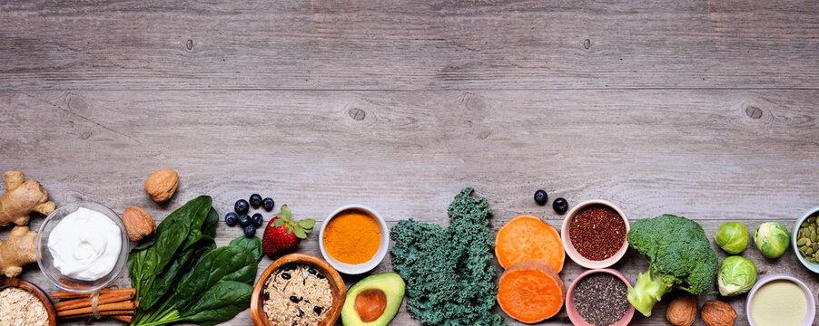 Set of healthy food ingredients. Top view bottom border on a wood banner background. Copy space. Super food concept with green vegetables, berries, whole grains, seeds, spices and nutritious items.