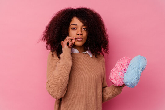 Young african american woman holding a sewing threads isolated on pink background with fingers on lips keeping a secret.