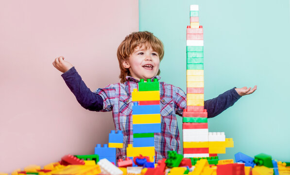 Little boy playing with lots of colorful plastic blocks constructor. Boy playing with construction blocks at kindergarten. Child playing with colorful toy blocks. Educational toys for young children