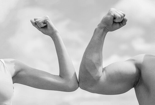 Sporty man and woman. Muscular arm vs weak hand. Vs, fight hard. Competition, strength comparison. Rivalry concept. Hand, man arm fist Close-up. Black and white
