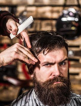 Man hairstylist. Beard man in barbershop. Hairstylist serving client at barber shop, bearded. Hairdresser, hair salon. Bearded man. Barber scissors, barber shop. Vintage barbershop, shaving