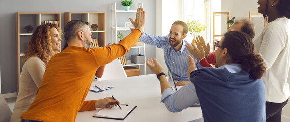 Obraz Happy successful multiracial business team clapping hands while two colleagues giving high fives gesture each other. Businesspeople laugh and cheer sitting at table in office on briefing meeting - fototapety do salonu