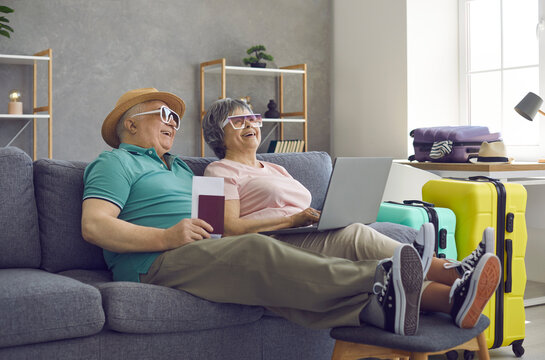 Happy senior couple getting ready for summer holiday trip, using laptop and laughing. Cheerful elderly husband and wife sitting on couch at home, visiting travel website or booking hotel room online