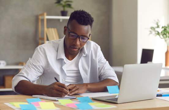Startup project development, research work, brainstorm. Young handsome minded black african american businessman sitting at home table front of laptop writing down ideas in notebook