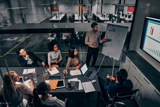 Business presentation. A group of handsome business people working in a spacious conference room in a large business center. Concept of startup, projects, planning, results, strategy.