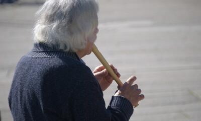 Fototapeta Miserável a pedir esmolas na rua - homem pobre idoso a tocar flauta na rua em troco de oferta de dinheiro para sobrevivência