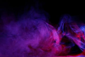 Fototapeta Art photo of purple smoke moves on black background. Beautiful swirling colorful smoke.