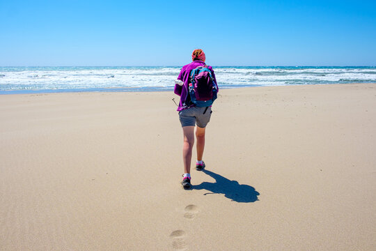 woman in summer with her backpack walking in the sand by the sea beach.