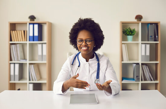 Head shot portrait of smiling african american female doctor wearing eyeglasses, uniform with stethoscope speaking, consulting patient online, looking at camera, making video call sitting at table
