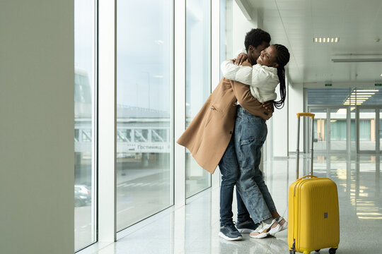 African couple hugging in airport. Black man give woman warm welcome embrace after travel, long vacation, business trip. Loving girlfriend and boyfriend or friends happy reunion at end of coronavirus