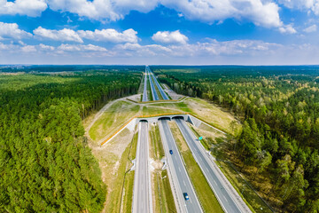 Fototapeta Expressway with ecoduct crossing - bridge over a motorway that allows wildlife to safely cross over the road, aerial top down view