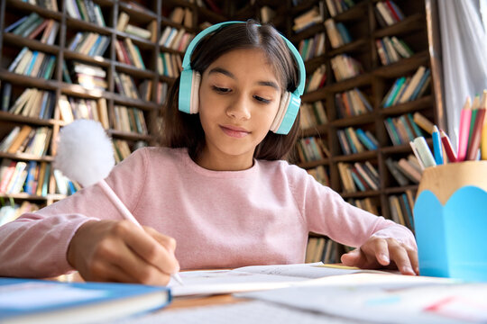 Cute indian schoolgirl with headphones learning online sitting at table listening to web seminar. Spanish junior student kid virtual learning writing in workbook doing homework at home classroom.