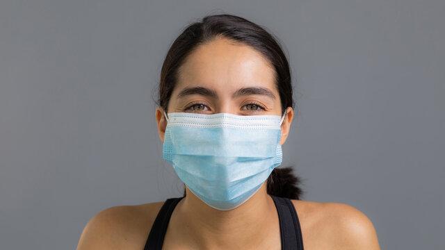 Joven bella mujer latina de ojos verdes sin maquillaje y cabello oscuro usando cubrebocas medical mask por coronavirus covid19 para cuidar la salud en mexico usando ropa deportiva negra con fondo gris