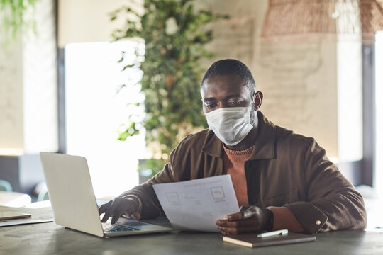 Portrait of African-American man wearing mask while using laptop and working in cafe or office, copy space
